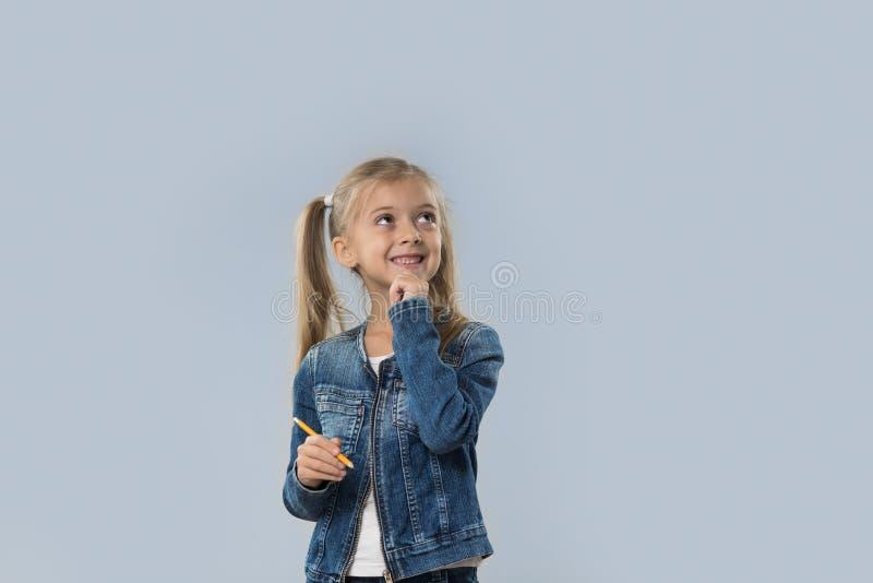 Escrita bonita do lápis da posse da menina que pensa a vista de sorriso feliz para copiar o espaço isolado foto de stock royalty free