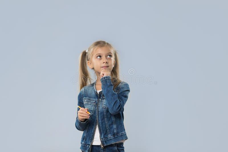 Escrita bonita do lápis da posse da menina que pensa a vista séria para copiar o espaço isolado imagens de stock