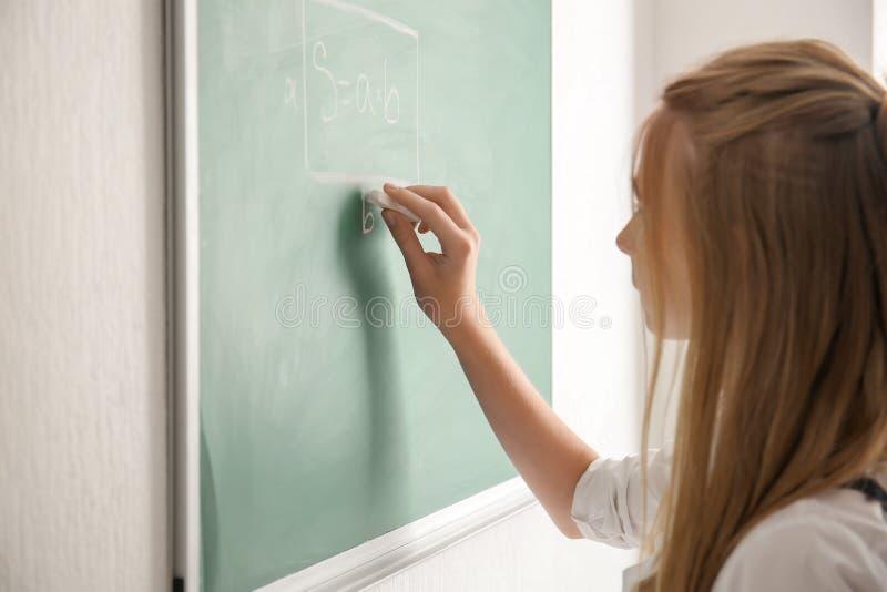 Escrita bonito da estudante com giz no quadro-negro foto de stock royalty free