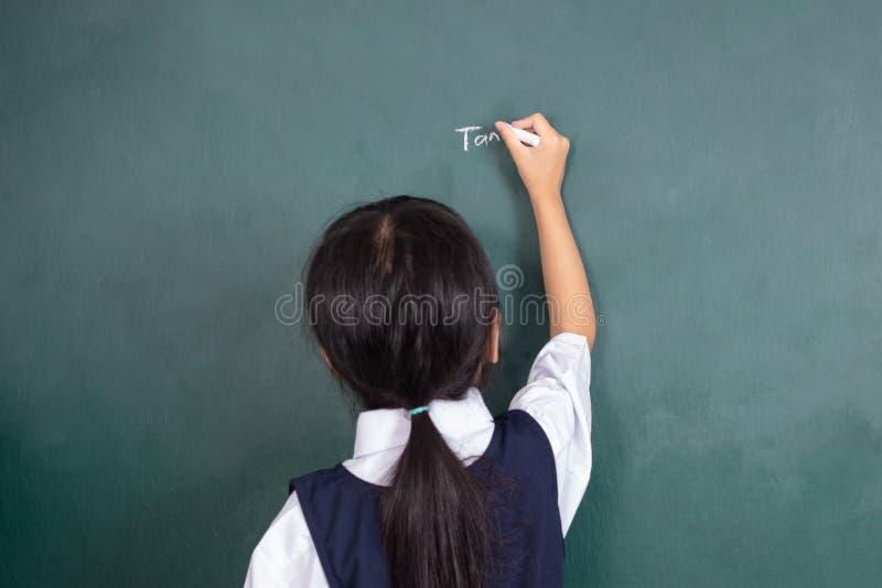 Escrita chinesa asiática da menina no quadro-negro imagens de stock royalty free