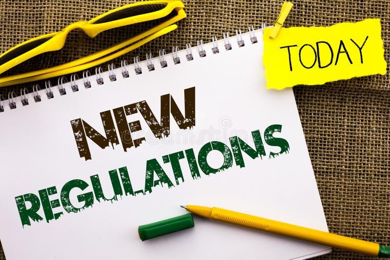 Escrita conceptual da mão que mostra regulamentos novos A mudança apresentando da foto do negócio das leis ordena especificações  fotos de stock