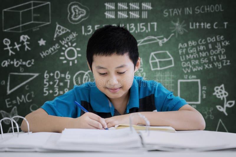 Escrita considerável do menino do preteen na sala de aula imagens de stock royalty free
