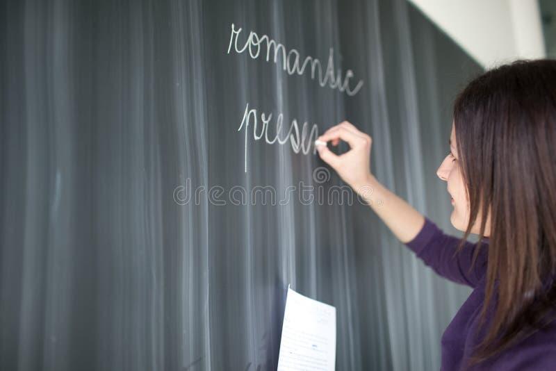 Escrita consideravelmente nova do estudante no quadro-negro fotos de stock