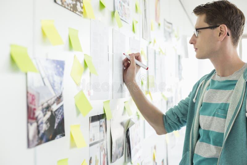 Escrita criativa do homem de negócios no papel no escritório imagem de stock