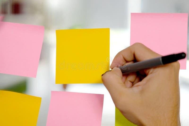 Escrita da bandeja da terra arrendada da mão em papéis de nota pegajosos coloridos vazios na placa de vidro no escritório, fontes imagem de stock royalty free