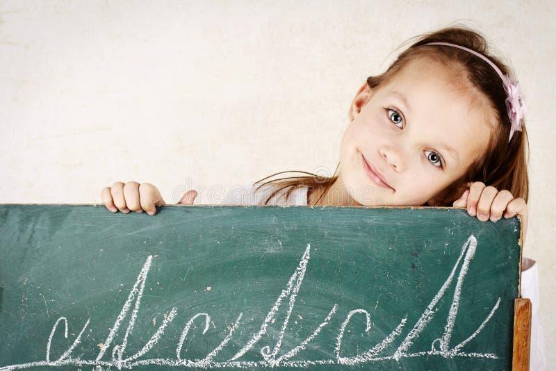Escrita da criança pequena no quadro-negro fotos de stock