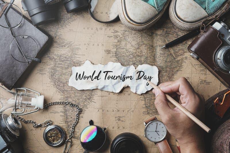 Escrita da mão do dia de turismo de mundo Fundo do conceito do curso Vista aérea dos acessórios do viajante no mapa velho do vint imagem de stock royalty free