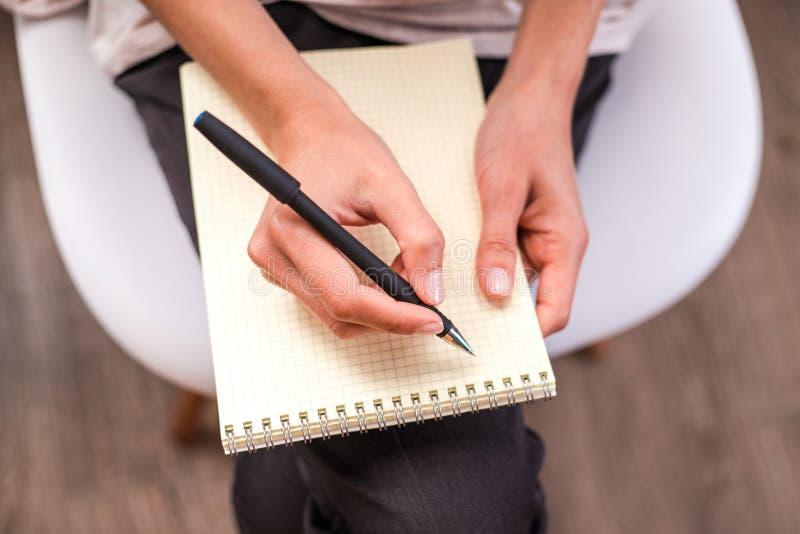 Escrita da mão da mulher em um caderno vazio imagem de stock