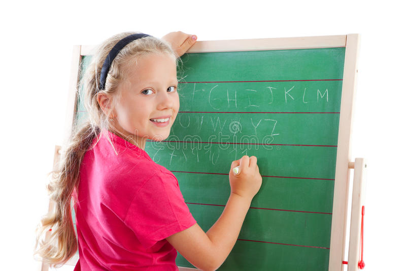 Escrita da menina da instrução no quadro-negro fotografia de stock