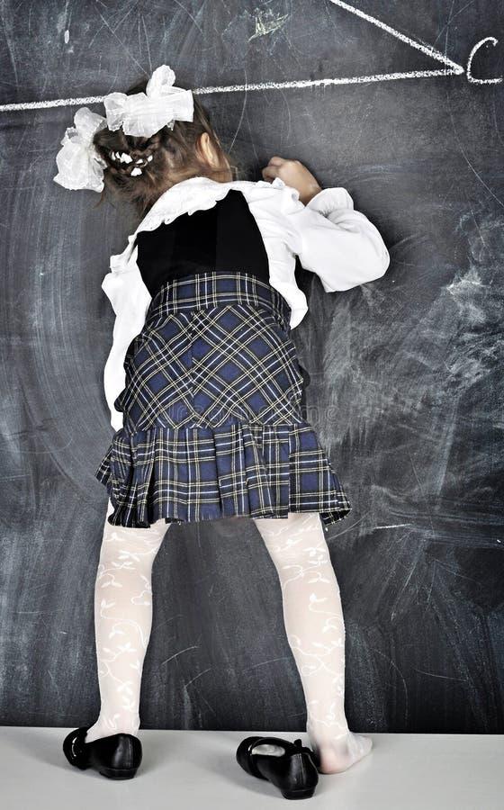 Escrita da menina no quadro-negro foto de stock