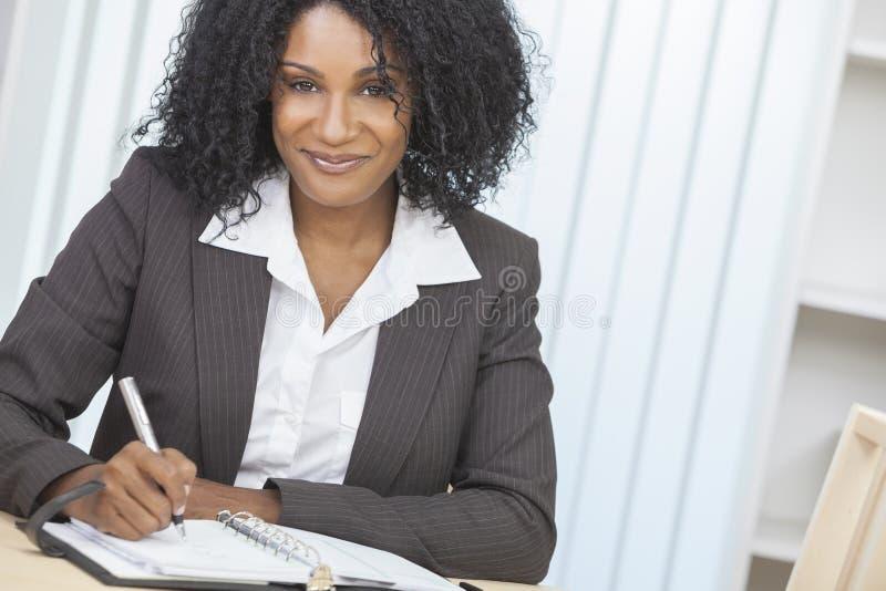 Escrita da mulher de negócios da mulher do americano africano imagem de stock