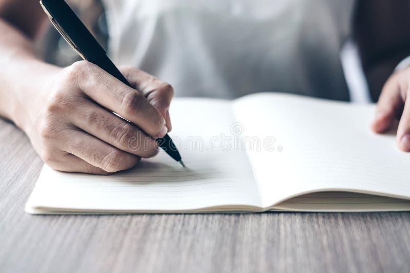 Escrita da mulher de negócios no caderno no escritório, mão da pena de terra arrendada da mulher com a assinatura no relatório do imagens de stock