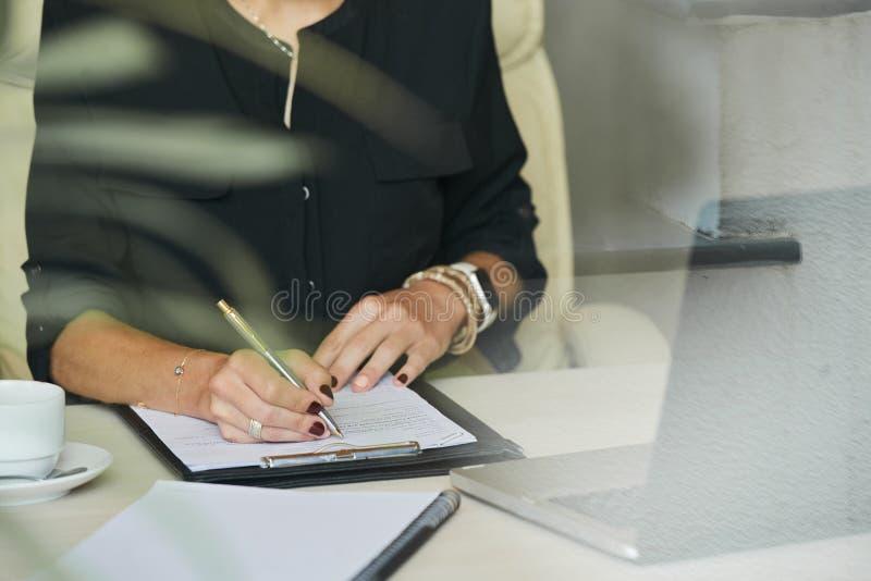 Escrita da mulher de negócios no documento fotografia de stock