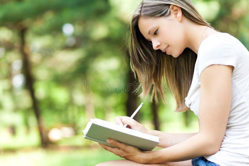 Escrita da mulher em seu diário no parque foto de stock royalty free