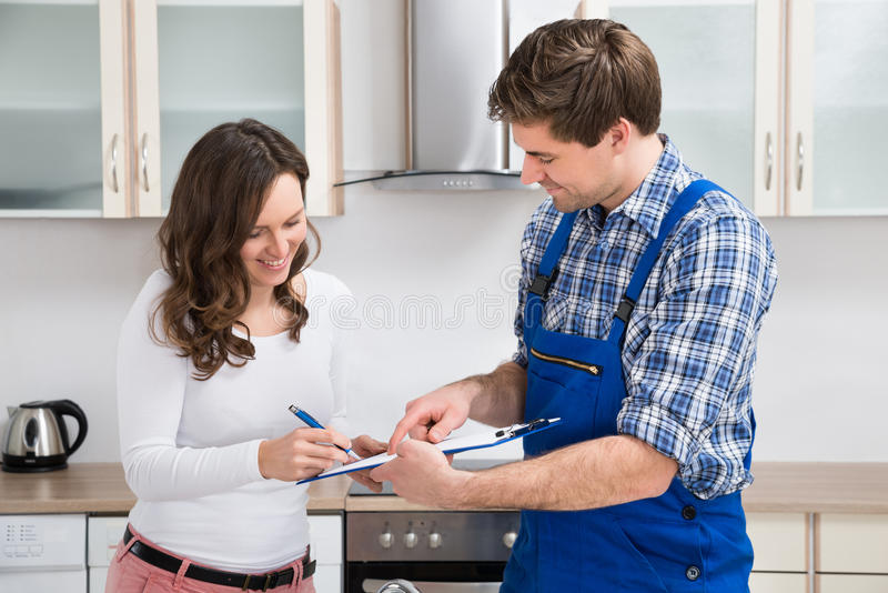 Escrita da mulher na prancheta com encanador In Kitchen Room imagem de stock