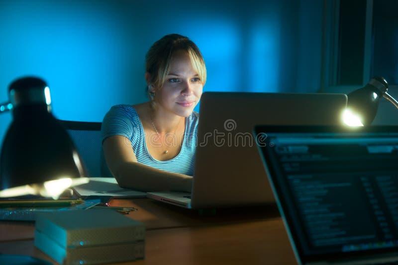 Escrita da mulher na rede social com PC tarde na noite fotos de stock royalty free