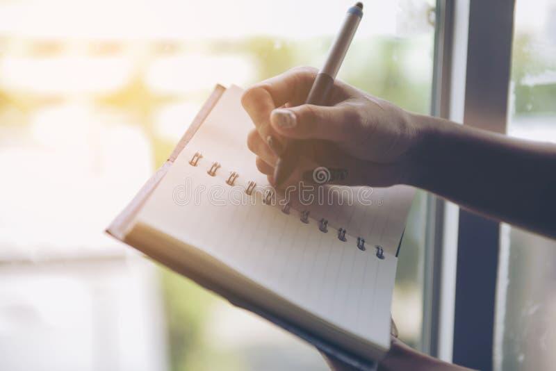 Escrita da mulher no caderno vazio na cama na manhã foto de stock royalty free