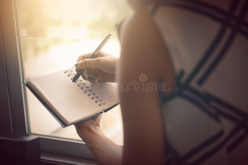 Escrita da mulher no caderno vazio na cama na manhã fotos de stock