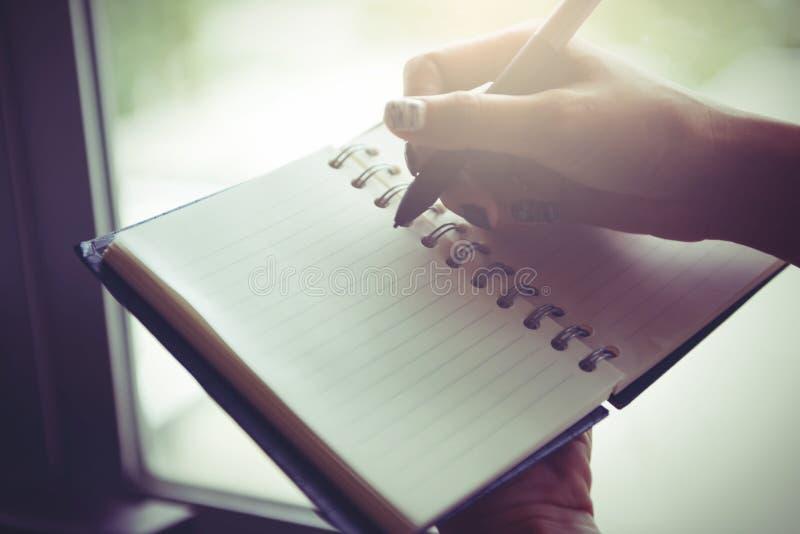 Escrita da mulher no caderno vazio na cama na manhã imagens de stock royalty free