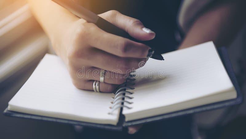 Escrita da mulher no caderno vazio na cama na manhã fotografia de stock royalty free