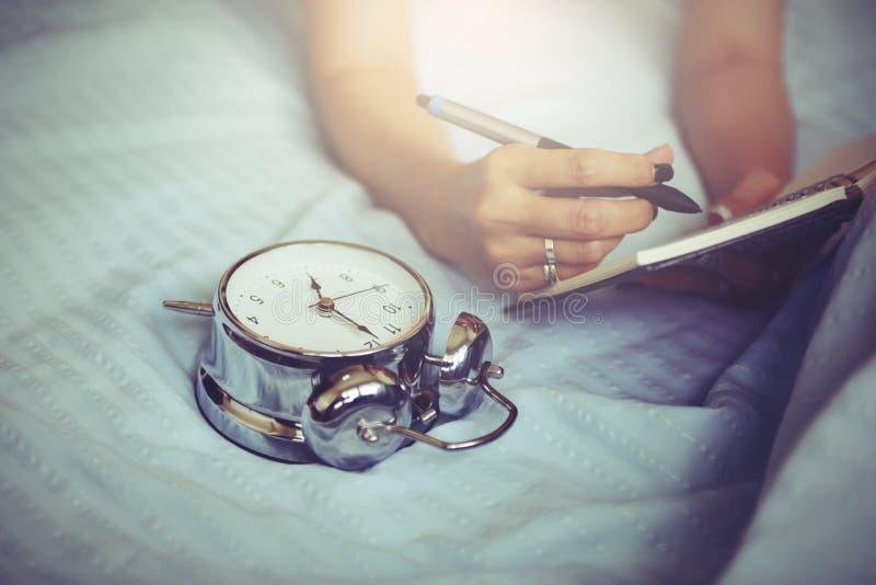 Escrita da mulher no caderno vazio na cama na manhã fotos de stock royalty free