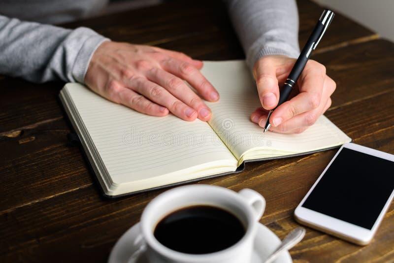 Escrita da mulher pela mão esquerda no caderno fotos de stock
