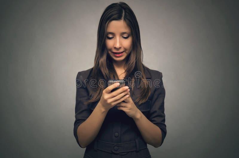 Escrita da mulher sms pelo telefone celular fotografia de stock