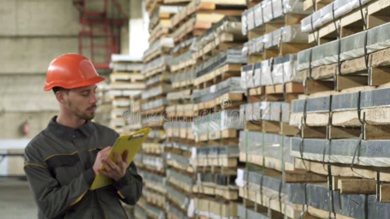 Escrita de passeio do trabalhador masculino considerável do armazém em sua prancheta fotografia de stock