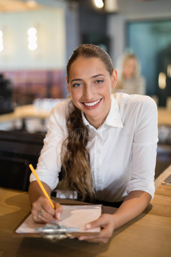 Escrita de sorriso do barman na prancheta no contador da barra imagens de stock royalty free