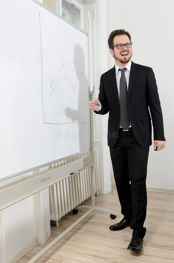 Escrita de sorriso do homem de negócios em uma placa branca foto de stock royalty free