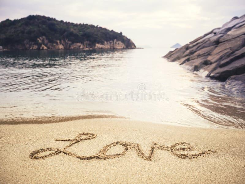 Escrita do amor no fundo do feriado da praia da areia fotos de stock royalty free