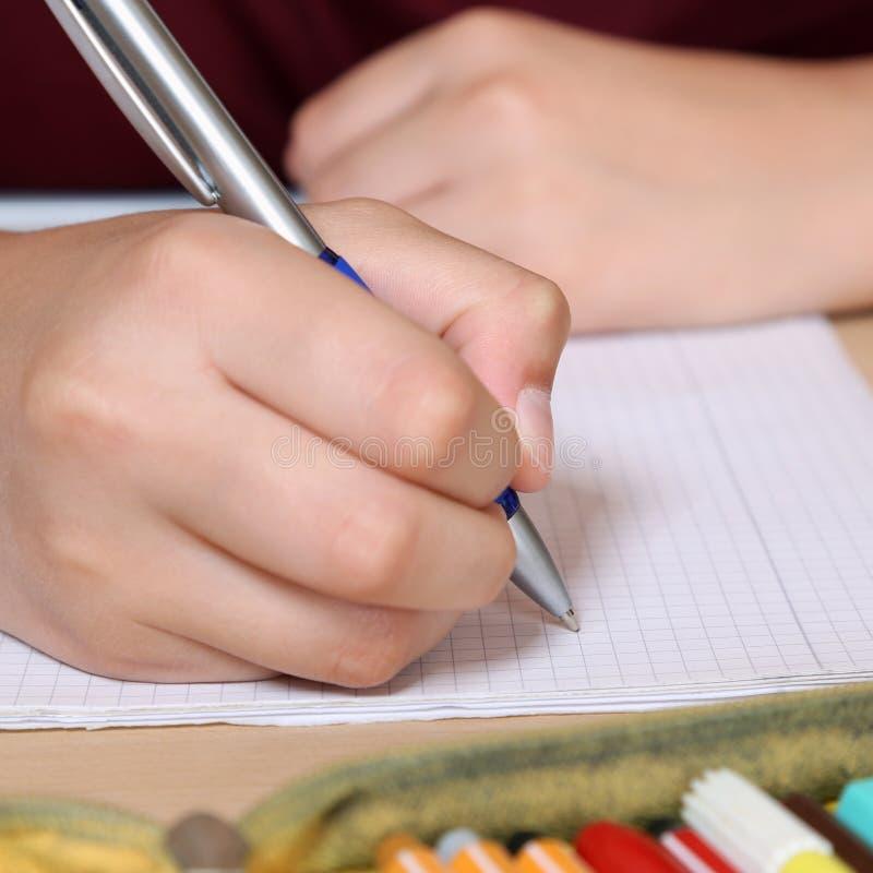 Escrita do estudante com mão em seu livro de exercício na escola fotos de stock royalty free