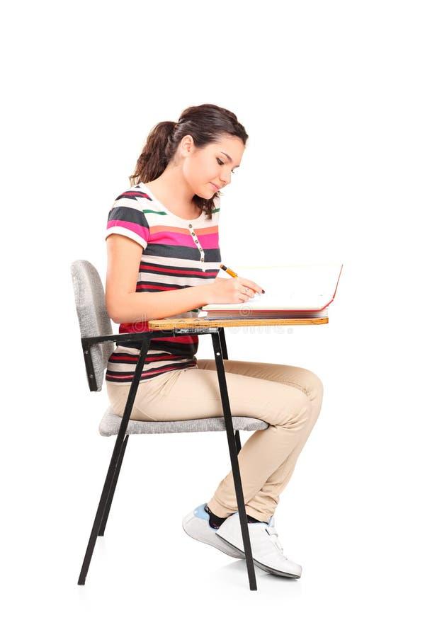 Escrita do estudante fêmea em um caderno fotos de stock royalty free