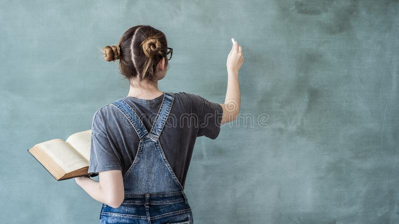 Escrita do estudante fêmea no quadro verde fotografia de stock royalty free