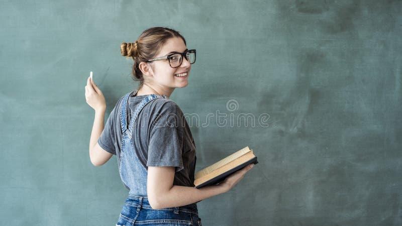 Escrita do estudante fêmea no quadro verde fotografia de stock