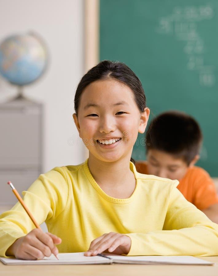 Escrita do estudante no caderno na sala de aula da escola fotografia de stock royalty free