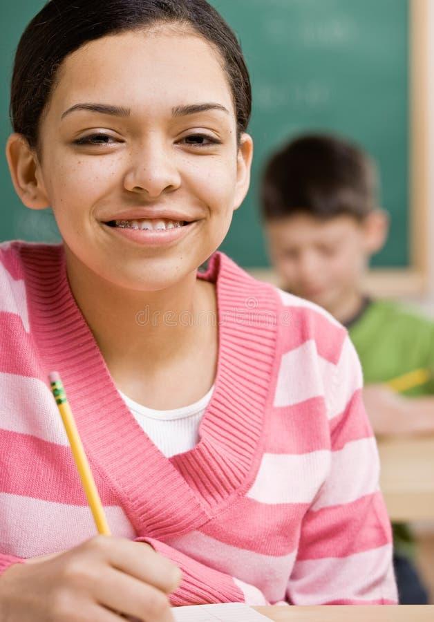 Escrita do estudante no caderno na sala de aula da escola imagens de stock