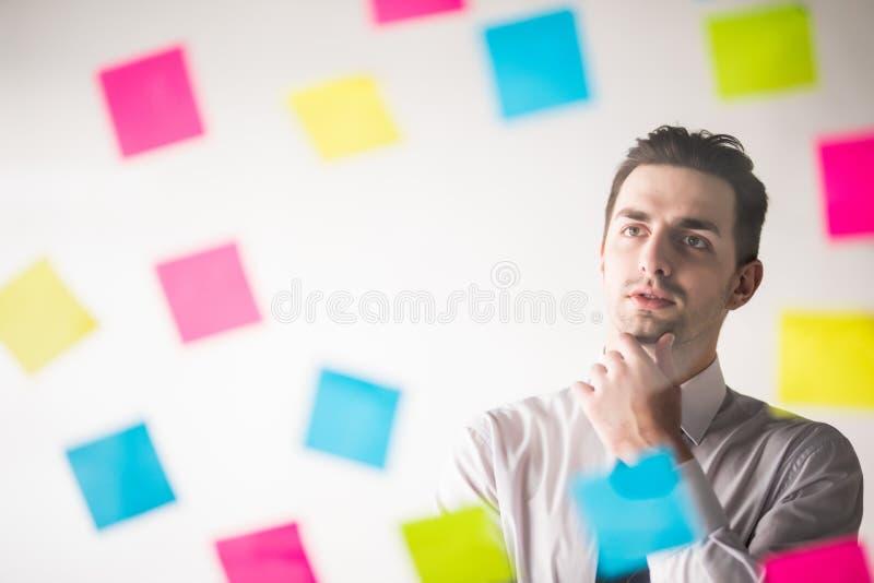 Escrita do homem de negócio em etiquetas no escritório e pensamento nelas foto de stock