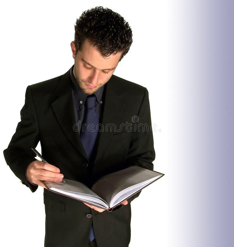 Escrita do homem de negócio no notebo imagem de stock