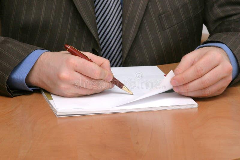 Escrita do homem de negócio no papel em branco fotografia de stock royalty free