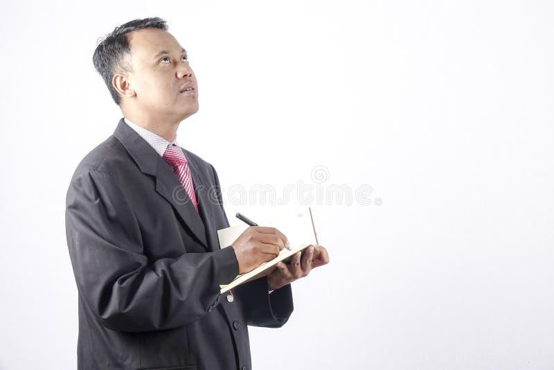Escrita do homem de negócios de Ásia no livro foto de stock royalty free