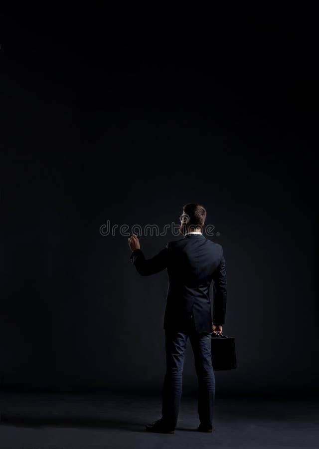 Escrita do homem de negócios algo sobre o fundo preto com copyspa foto de stock royalty free