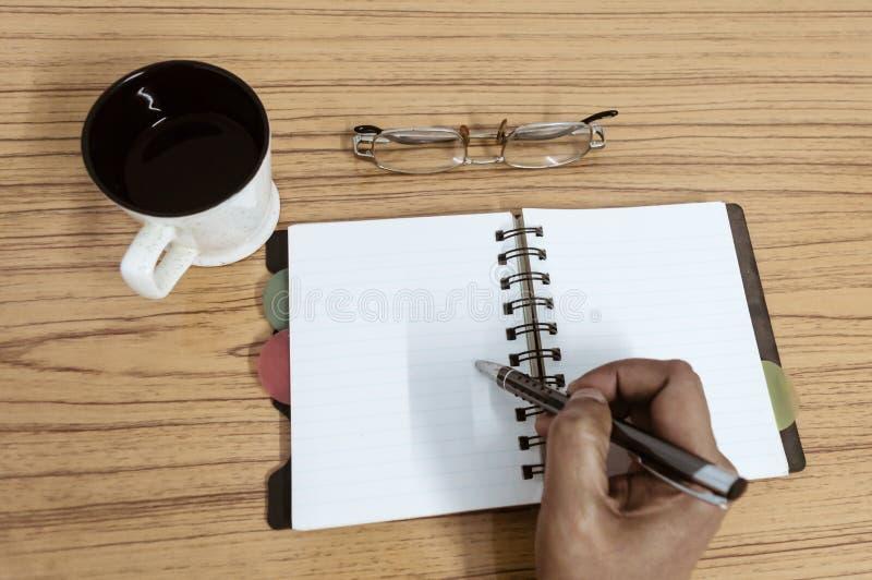 Escrita do homem de negócios em seu diário Caderno aberto com as páginas vazias ao lado da xícara de café e dos monóculos na tabe foto de stock royalty free