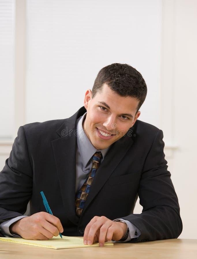 Escrita do homem de negócios na almofada legal que toma notas fotos de stock