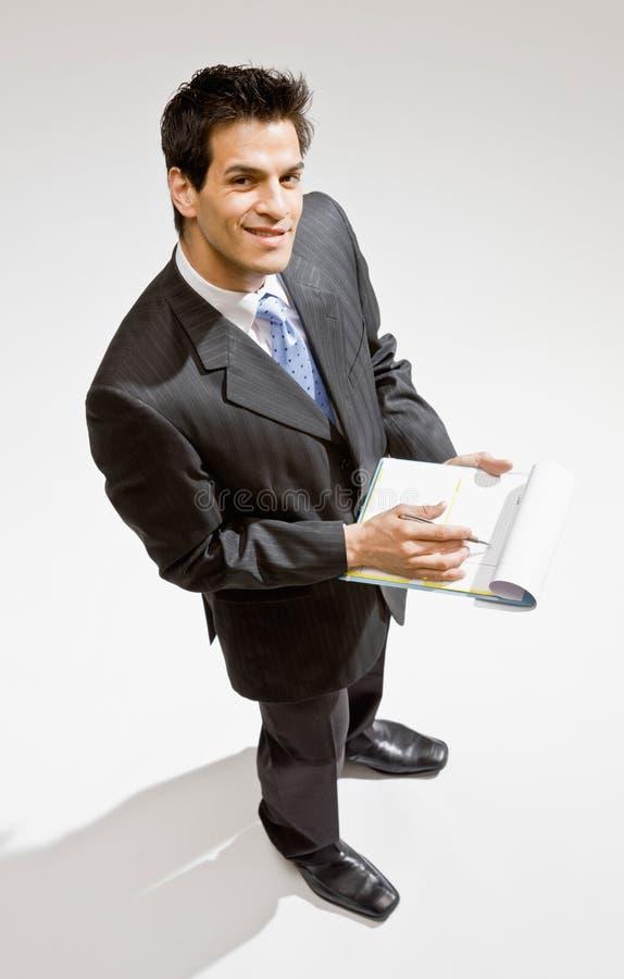 Escrita do homem de negócios na prancheta fotos de stock