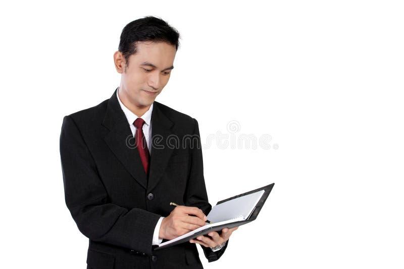 Escrita do homem de negócios no caderno, isolado no branco imagens de stock royalty free