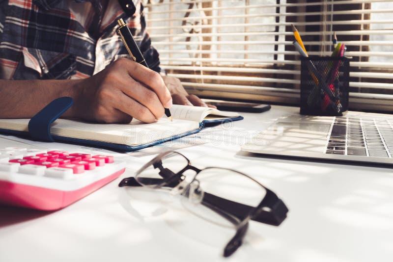 Escrita do homem de negócios no caderno na tabela de madeira fotografia de stock