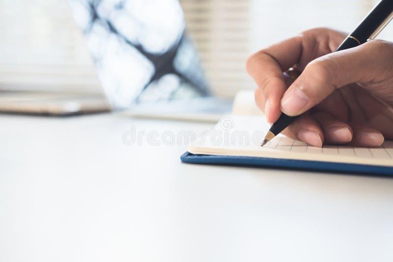 Escrita do homem de negócios no caderno na tabela de madeira fotografia de stock royalty free