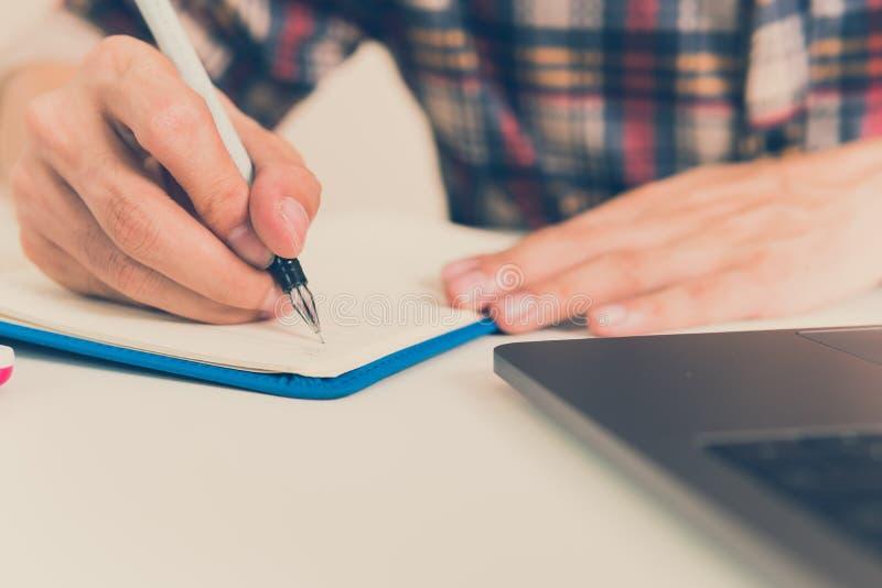 Escrita do homem de negócios no caderno na tabela de madeira imagem de stock