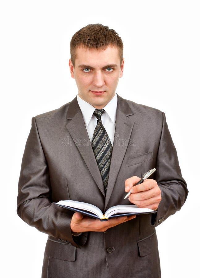 Escrita do homem de negócios no diário do negócio fotografia de stock
